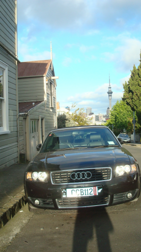 Une Audi dont la plaque affiche firement la Fougre No Zlandaise ainsi que le drapeau du pays du long nuage blanc - dsormais, cest aussi la marque rouge dpos par un Cantalou de passage. La scne se passe dans une rue de Ponsonby, quartier en vogue dAuckland - en arrire plan la Sky Tower, qui surplombe la ville.